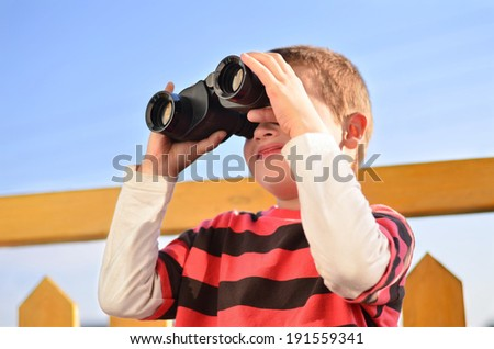 Curious boy with binoculars on a balcony - stock photo