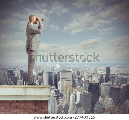Curious businessman looks beyond with his binoculars - stock photo