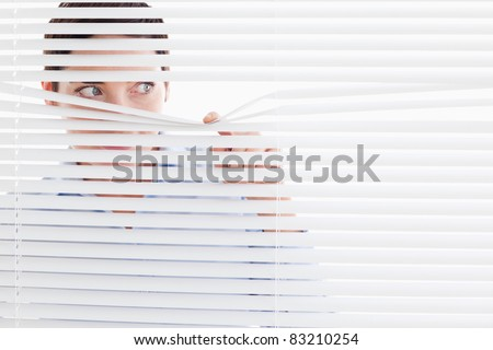 Curious businesswoman peeking out of a window in an office