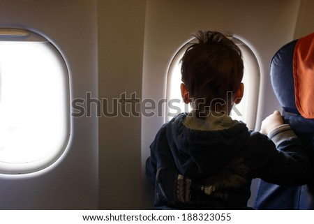 Curious child looking through window in the airplane - stock photo