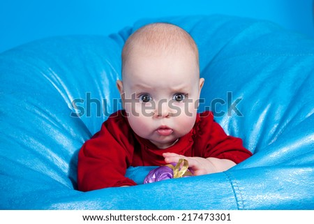 Curious chubby baby looking straight at the camera. - stock photo