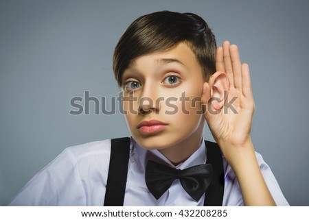 Curious Disappointed boy listens. Closeup portrait child hearing something, parents talk, hand to ear gesture isolated grey background. Human face expression, emotion, body language, life perception - stock photo