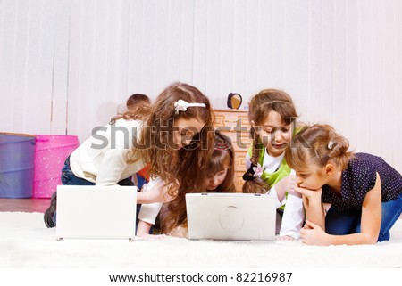 Curious elementary school-aged girls busy playing computer games - stock photo