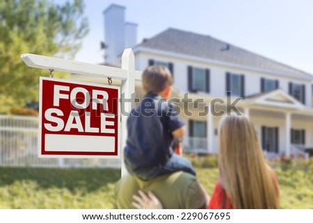Curious Family Facing For Sale Real Estate Sign and Beautiful New House.