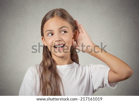 Curious girl listens. Closeup portrait teenager hearing something, parents talk, hand to ear gesture isolated grey wall background. Human face expression, emotion, body language, life perception - stock photo