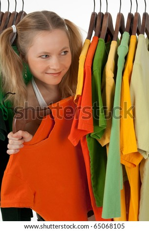 Curious girl looking out of the clothes rack in a store, choosing what to buy. - stock photo
