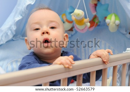 curious infant in a cradle