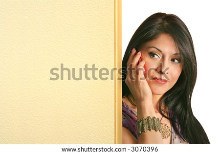 curious latino girl with a pink cellphone peeking from behind a light partition board. perfect to put your text on there.
