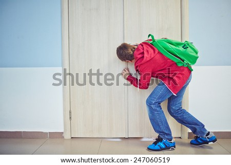 Curious learner with backpack peeping into keyhole of classroom door - stock photo