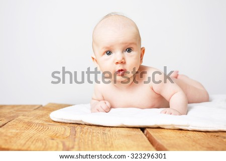 Curious little baby boy lying on wooden floor. - stock photo