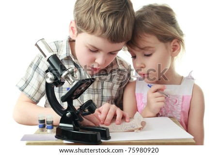 Curious little boy and girl draw diagram near black microscope - stock photo