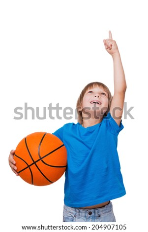 Curious little boy. Cheerful little boy holding basketball ball and pointing up while standing isolated on white - stock photo