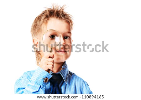 Curious little boy in spectacles is looking through a magnifying glass. Isolated over white background. - stock photo