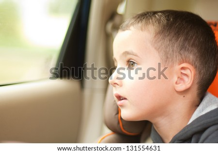 Curious little boy in the car watching the window sitting in safe chair - stock photo