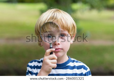 Curious little boy looking through magnifying glass on a sunny day - stock photo