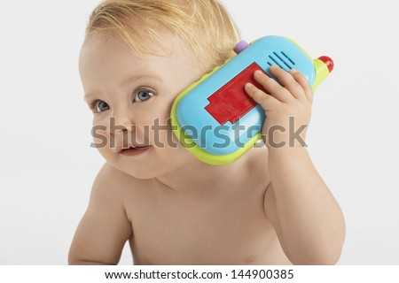 Curious little boy using toy phone isolated on white background - stock photo