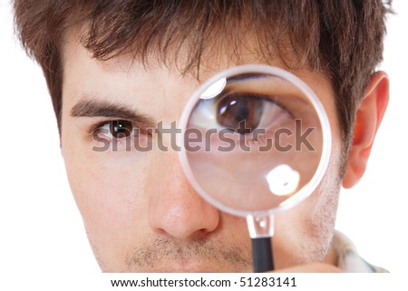 Curious man examining with magnifying glass