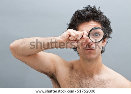 Curious man examining with magnifying glass - stock photo