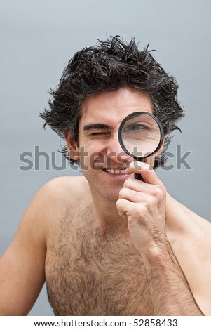 Curious man holding a magnifier over his eye - stock photo
