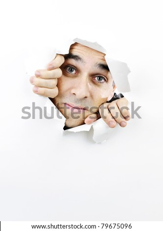 Curious man looking through hole torn in white paper - stock photo
