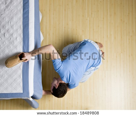Curious man peering underneath bed in search of his slipper - stock photo