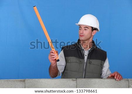 Curious mason stood by wall - stock photo