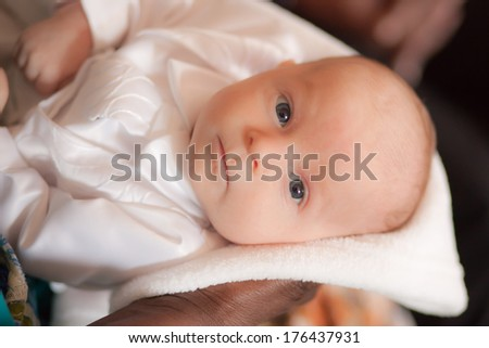 Curious newborn baby boy with bright blue eyes looking straight ahead in a white tuxedo baby blessing outfit held by an African American woman - stock photo