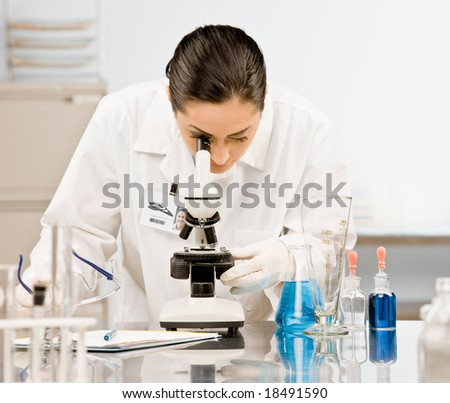 Curious research scientist in lab coat and rubber gloves looking at specimen under microscope in laboratory - stock photo