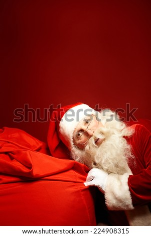 Curious Santa Claus keeping his ear by big red sack with Christmas presents - stock photo