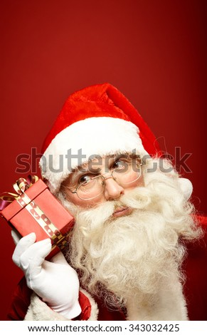Curious Santa with small gift-box by his ear - stock photo