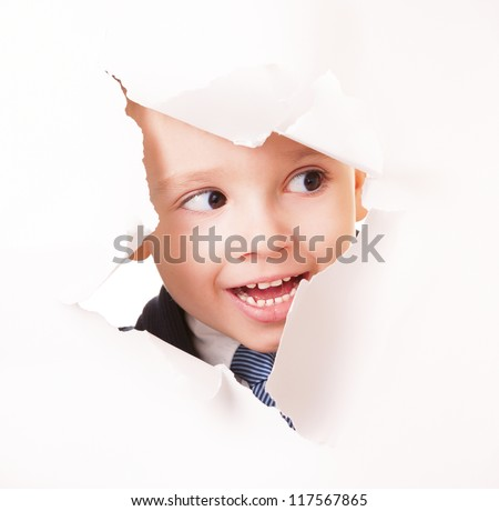 Curious scout agent boy spying through the hole in the paper - stock photo