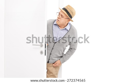 Curious senior gentleman looking at something behind a white door isolated on white background - stock photo
