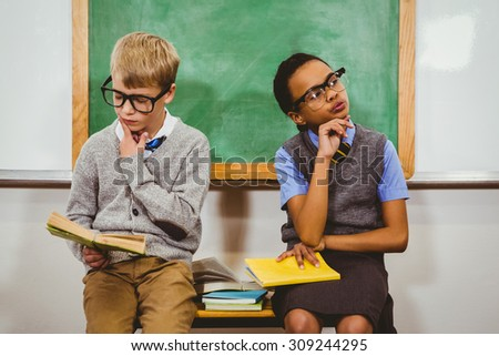 Curious students reading books in class at the elementary school - stock photo