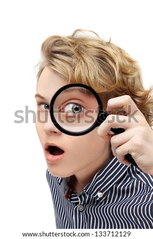 Curious teenage boy looking through magnifying glass at the camera.White background - stock photo