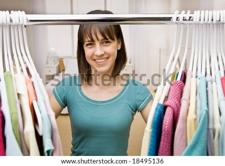 Curious teenager searching in closet for something to wear - stock photo