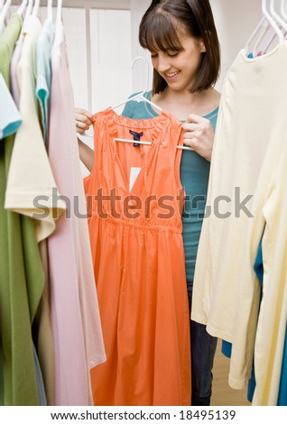 Curious teenager searching in closet for something to wear holding up dress - stock photo