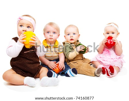 Curious toddlers tasting colorful peppers - stock photo