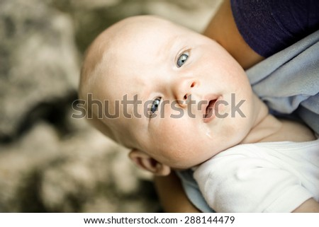 Curious, well fed baby with blue eyes looking around with great wonder and fascination, resting in mothers arms. Natural childhood, outdoor lifestyle, family values concept.  - stock photo