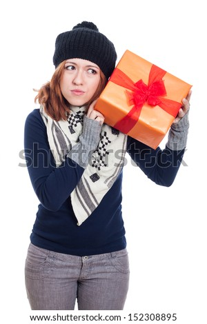 Curious winter woman holding present, isolated on white background. - stock photo