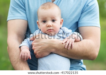 curious with funny face little boy in his father's hands wearing blue clothes - stock photo