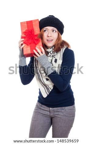Curious woman in winter clothes holding present, isolated on white background. - stock photo
