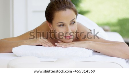 Curious woman on spa table wrapped in white towels - stock photo