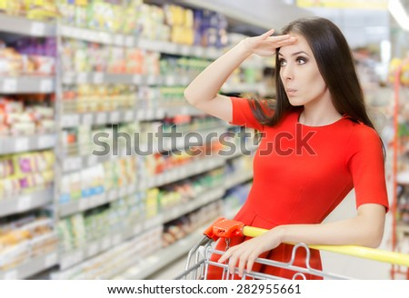 Curious Woman Shopping  at The Supermarket - Portrait of a young girl in a market store with a shopping cart - stock photo
