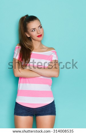 Curious Woman. Young woman in pink striped shirt and jeans shorts standing with arms crossed and looking away. Three quarter length studio shot on teal background. - stock photo