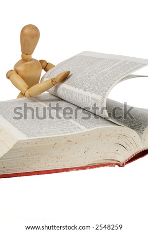 """Curious wooden person flipping through a book. Out of focus is a dictionary page with """"self"""",  isolated white - stock photo"""