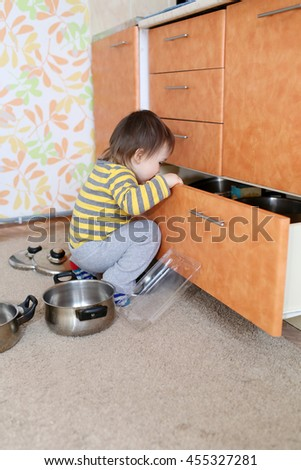 curious 1 year baby looks into drawer on kitchen