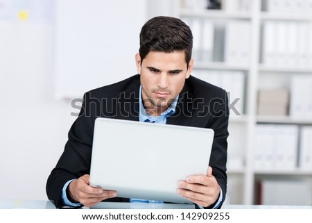 Curious young businessman holding laptop at desk in office - stock photo