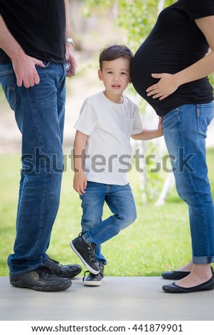 Curious Young Mixed Race Son With Ear on Pregnant Belly of Mommy with Daddy Nearby. - stock photo