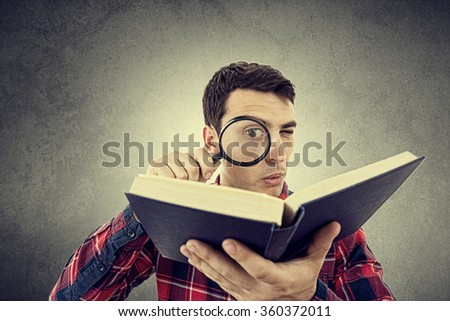 Curious young student man holding book with a magnifying glass.Perplexed Young man student holding magnifying glass and a book isolated over grey background. - stock photo