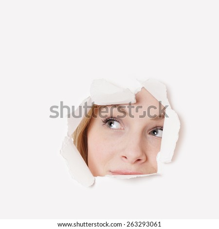 curious young woman peeking through hole and looking up  - stock photo